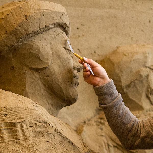 Artista che lavora la sabbia